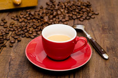 Red mug espresso coffee and a spoon. In front of a beans and coffee mill Stock Images