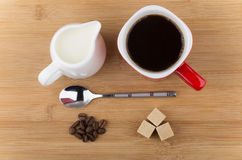Red mug with espresso, spoon, coffee beans and milk jug Royalty Free Stock Image