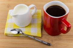 Red mug with espresso, white jug of milk Royalty Free Stock Images