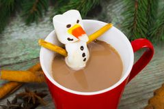 Red mug with hot chocolate with melted marshmallow snowman Royalty Free Stock Photo