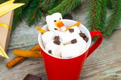 Red mug with hot chocolate with melted marshmallow snowman Stock Photos