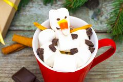 Red mug with hot chocolate with melted marshmallow snowman Stock Image