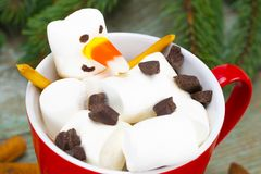 Red mug with hot chocolate with melted marshmallow snowman Stock Images
