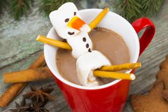 Red mug with hot chocolate with melted marshmallow snowman Royalty Free Stock Photos