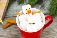Red mug with hot chocolate with melted marshmallow snowman Royalty Free Stock Photography
