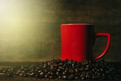 Red mug on a pile of fresh roasted coffee beans over wooden table. Coffee break and beverage concept Stock Photos
