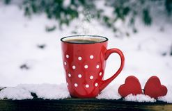 Red mug with polka dots with hot black coffee. And two wooden hearts, vintage toning royalty free stock image