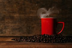 Red mug with steam on a pile of fresh roasted coffee beans over wooden table. Coffee break and beverage concept Stock Images