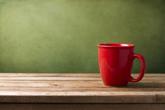 Red mug on wooden table Royalty Free Stock Images