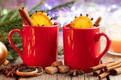 Red mugs of hot mulled wine, Christmas tree branches and garland bokeh lights on background. stock photos