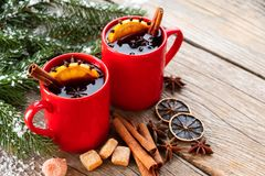 Red mugs of hot mulled wine with spices and Christmas tree branches covered with snow. Copy space for text. royalty free stock photo