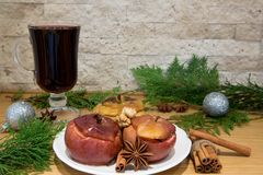 Red mulled wine and bake apples. Silver Christmas balls decoration. Red mulled wine and baked apples with melting honey, nuts and spices, cinnamon and anise royalty free stock image