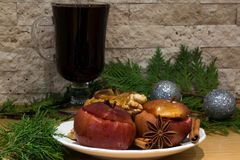 Red mulled wine and bake apples. Silver Christmas balls decoration. Red mulled wine and baked apples with melting honey, nuts and spices, cinnamon and anise stock image