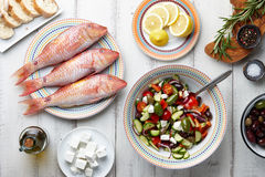 Red mullet fish and mediterranean dishes cooking. Raw mullet fish, greek salad and other mediterranean ingredients on white wooden table Royalty Free Stock Photos