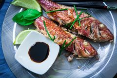 Red mullet fish style. Two red mullet with chili pepper and soja sauce on plate with chopstick Stock Photo