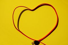 Red multi charger cable heart shape on yellow background royalty free stock photography