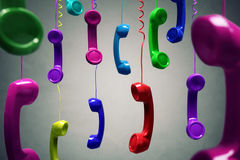 Red and multi-coloured telephone receiver hanging Royalty Free Stock Photos