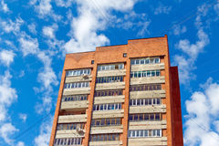 Red multi-storey building with wires on the background of blue s Royalty Free Stock Photos