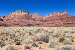 Red multicoloured sandstone mountains and dry shrubs in Glen Canyon National Recreation Area royalty free stock photos