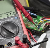 Red multimeter on printed-circuit boards Stock Images