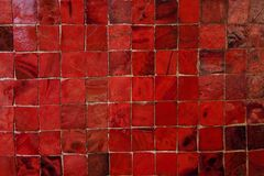 Red Murano Glass Tiles Pattern. Closeup of a wall decorated with Murano glass mosaic tiles in red hues. Nice pattern with bright colors for backgrounds textures Royalty Free Stock Photo