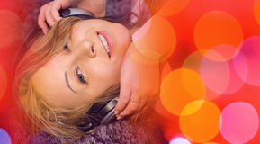 Red music background and pretty young woman listening music, looking at camera Stock Photos
