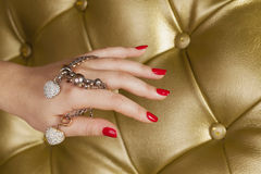 Red nail hand with a two hart bracelet royalty free stock image