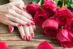 Red nail manicure with red roses around Stock Images