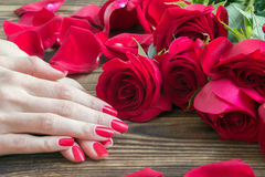 Red nail manicure with red roses around Stock Photo