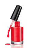 Red nail polish bottle with drop on white Stock Photos
