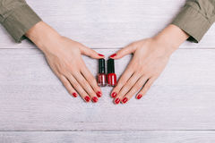 Red nail polish and female hands with manicure Stock Images