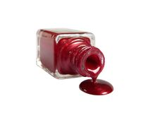 Red nail polish is flowing from the bottle Royalty Free Stock Photo