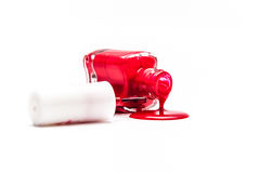 Red nail polish pouring from overturned bottle Stock Photo