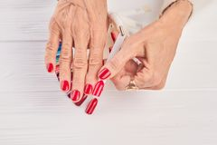 Red nail sample in female hand. Old woman hand with red manicure holding red nail sample. Well-groomed femal hands in beauty salon stock photo