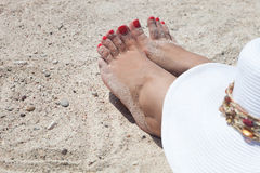 Red nailed toes of a woman on the beach Royalty Free Stock Photos