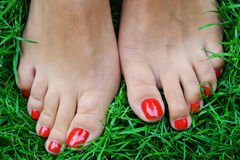Red nails. On the green grass Stock Image