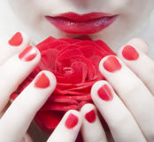 Red nails. Woman with red nails and lips holding rose Royalty Free Stock Photography