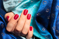 Red nails and blue silk. Hand of the girl with red nails over blue silk stock photography
