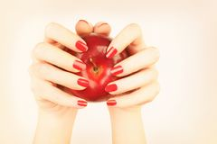 Red nails manicure hand with apple Royalty Free Stock Photo