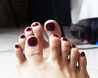 Red nails after pedicure. Women feet after pedicure with red nails and dry leg royalty free stock photography