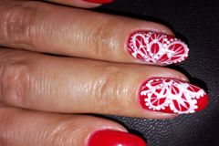 Red nails with white pattern. royalty free stock photo