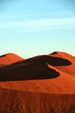 Red namib dune under lightblue sky. Namib dunes throughing there shadow under the mornign sun of the desert. The lightened age constrasts with the dark shadows Stock Images