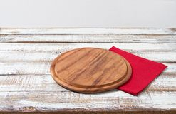 Red Napkin and cutting board on wooden table closeup. Selective focus royalty free stock photo