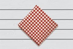 Red napkin on a wooden background. Plaid gingham tablecloth for cafe and restaurant design.  Stock Photo