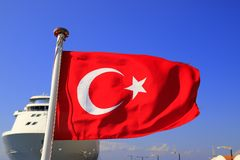 Red National Flag of Turkey with a half month and a star against the blue sky and a large white ocean liner, Turkish state symbol stock photos