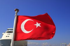 Red National Flag of Turkey with a half month and a star against the blue sky and a large white ocean liner, Turkish state symbol stock image