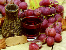 Red natural jucie homemade wicker bottle and grapes Stock Images