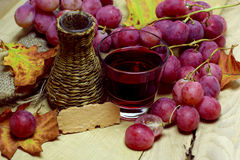 Red natural jucie homemade wicker bottle and grapes Stock Photo