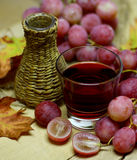 Red natural wine homemade wicker bottle and grapes Royalty Free Stock Images