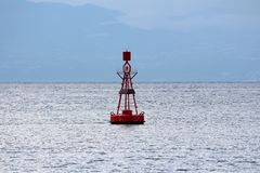 Red navigational buoy with light on top and small solar panels for charging surrounded with restless sea. On cloudy day stock photos